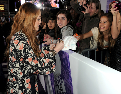 Miley Cyrus poses with fans and  signs autographs (photos)