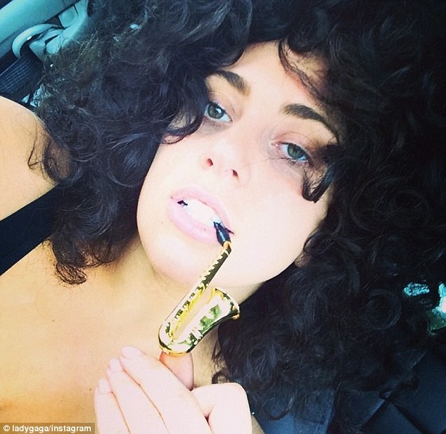 Lady Gaga Poses Biting Into A Saxophone-Shaped Tobacco Pipe